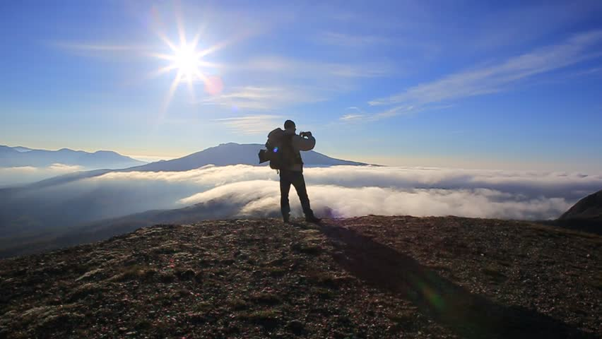Traveller man with backpack stands at the top of the mountain with blue sky and sun above and clouds fast floating below and takes a picture of beautiful landscape with his smartphone. #22050808