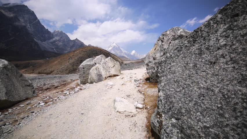 Walking along Dingboche-Lobuche path in Khumbu valley, Himalaya, Nepal. View of Khumbu icefall. Pumo Ri is on the left, Nuptse mountain is on the right. Amazing blue sky with white clouds.