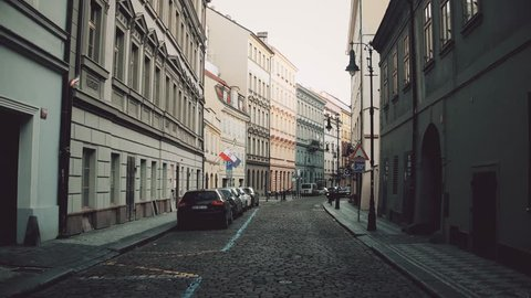 PRAGUE, CZECH REPUBLIC - DECEMBER 3, 2016. 4K steadicam video of a narrow cobblestone paved street with parked cars. Old european city view