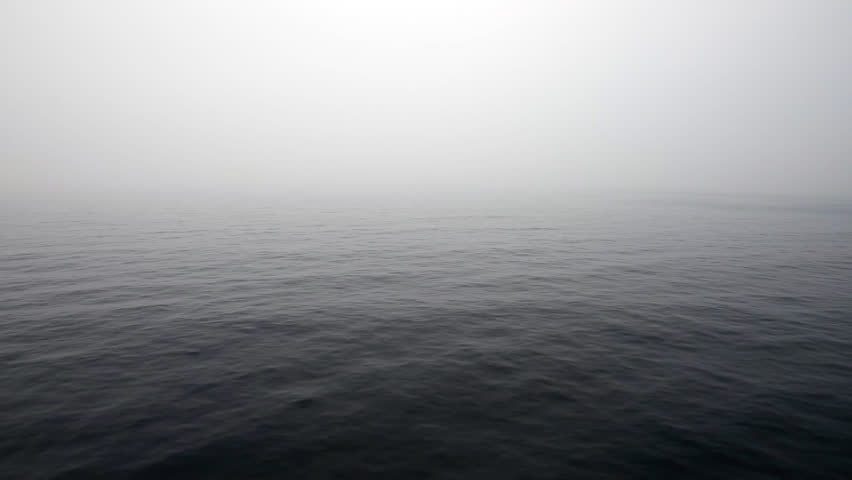Foggy morning at moody sea with cloudy sky, view form a moving cruise ship