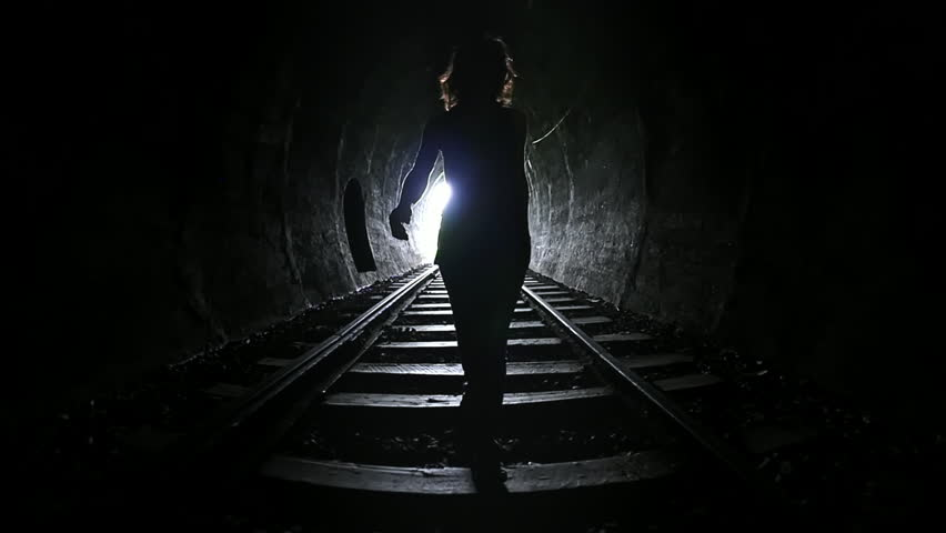 Silhouette of woman walking through dark railway tunnel conceptual slow motion video