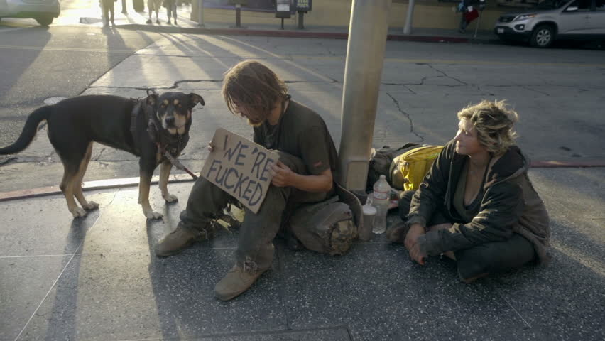 LOS ANGELES - OCT 19, 2016: Man And Woman With Dog On Street With We're Fucked Sign Homeless Couple In Los Angeles CA. Homelessness in LA grew by 12 percent between the years 2013 and 2015.