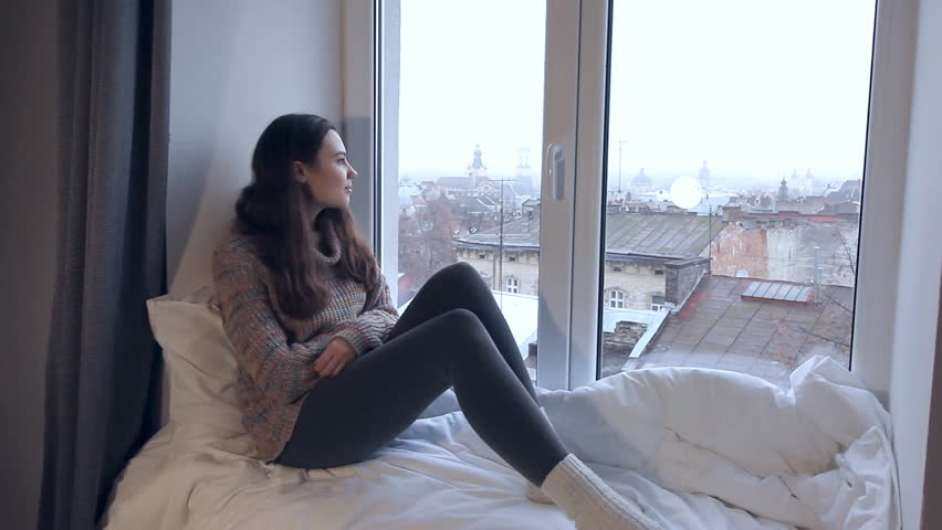 Portrait of young girl in sweater sitting on windowsill and looking through window on city roofs. Landscape of a old european city through the window. | Shutterstock HD Video #22149499