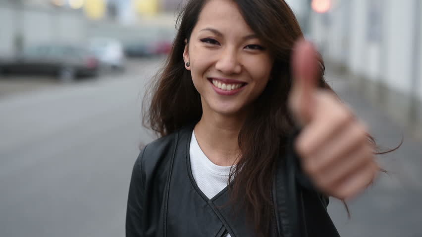 Beautiful young asian woman smiling with thumb up outdoor in the city, looking at camera – ok, yes, positive concept