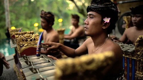 Asian Balinese musician gamelan group playing in traditional dress in a ceremonial celebration performance Indonesia South East Asia