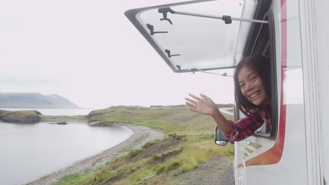 Travel woman in mobile motor home RV campervan waving hand saying hello hi looking out window of car on Iceland in recreational vehicle. Girl enjoying coffee in Icelandic nature landscape.