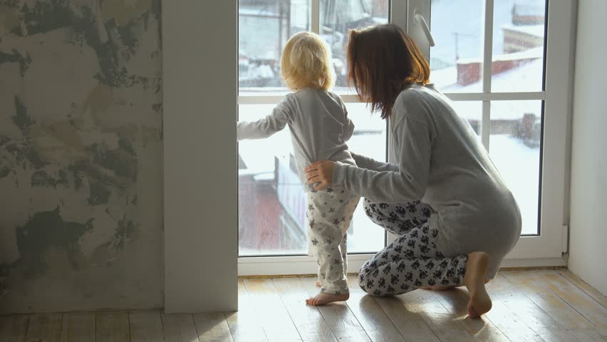Little baby and her mother looking out the window | Shutterstock HD Video #22181758