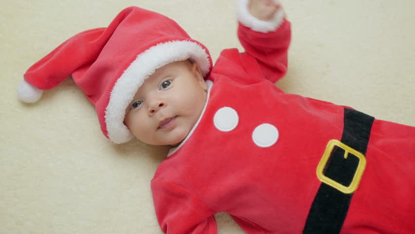 f5dc35186 4k00:27Cute 2-month-old baby boy in red Santa Claus on woolen ...