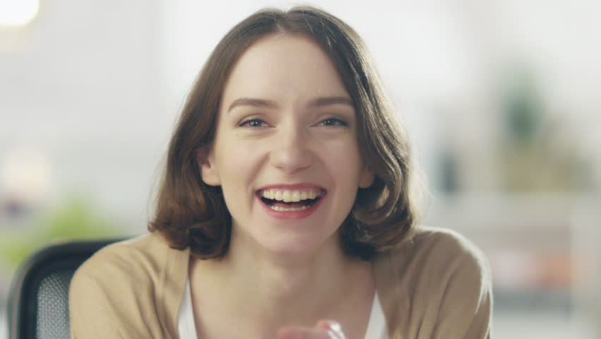 Beautiful Young Woman Laughs on the Camera. Her Background is Bright and Blurred. Shot on RED Cinema Camera in 4K (UHD).