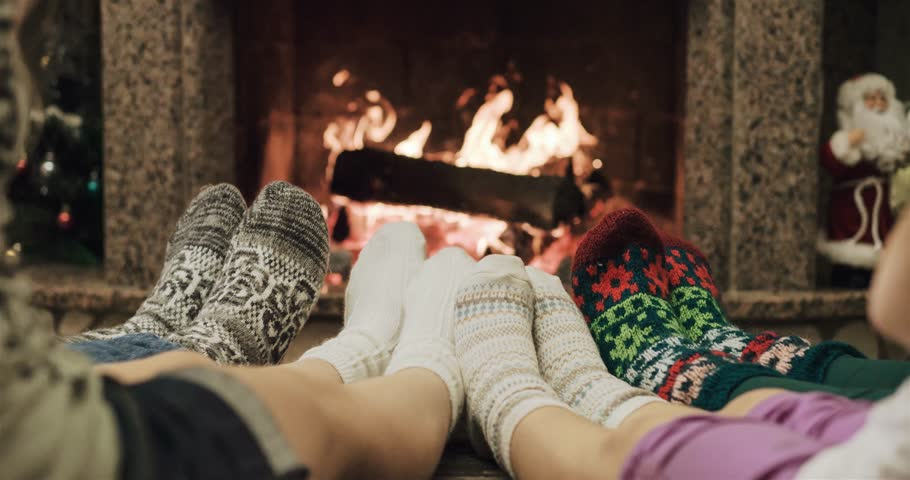 Cinemagraph - Feet in woolen socks warming by cozy fire in Christmas time in slow motion. Loop. Family with two kids warming their feet by the fireplace in winter time. 120 fps 4k motion photo. | Shutterstock HD Video #22215103