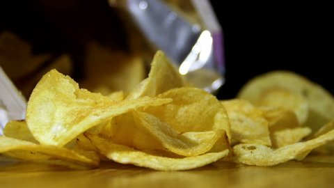 Potato Chips In Package Rotating. Open package of potato chips on the table and rotates. Close-up of yellow delicious chips randomly lying on a table. Excellent Footage for themes: Harmful food, fast
