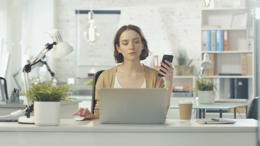 Portrait Shot of a Creative Woman Sitting at Her Desk. She Holds Smartphone and Consults Her Notebook. She Sits in a Light and Modern Office. Shot on RED Cinema Camera in 4K (UHD). | Shutterstock HD Video #22232065