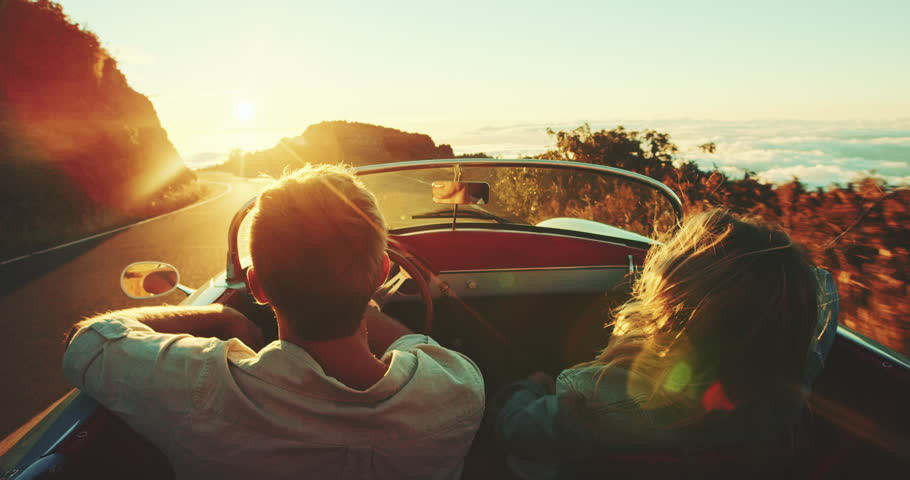 Happy couple driving on country road into the sunset in classic vintage sports car | Shutterstock HD Video #22242868