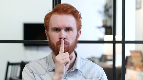 Gesture of Silence by Young Man, Finger on Lips