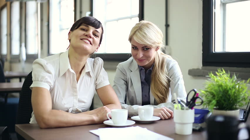 Two happy young businesswomen chatting in the office    Shutterstock HD Video #2224759