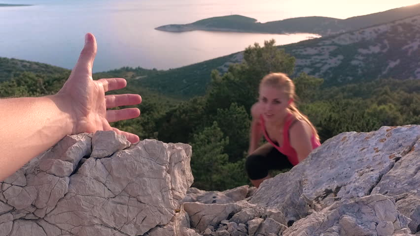 Slow motion - Closeup of a male's hand stretching out and helping happy female friend reach the rock mountain top. POV of a man giving hand to a woman and helping her reach the seaside mountain top