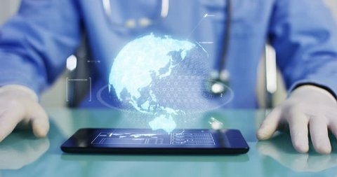 A physician, surgeon, examines a technological digital holographic plate represented the patient's body, the heart lungs, muscles, bones. Concept: Futuristic medicine,assistance world, and the future.