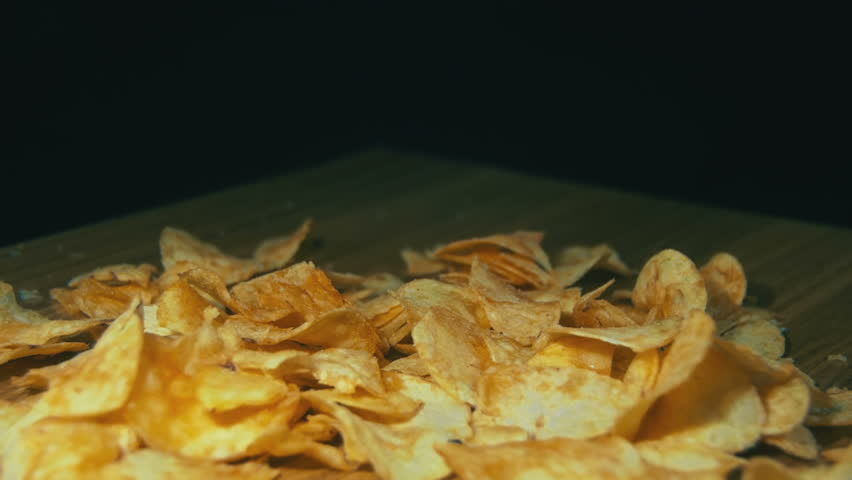 Potato Chips are Falling on a Wooden Table on Black Background. Slow Motion in 96 fps. Potato chips are rotated on a black background. Close-up of yellow delicious chips randomly lying at the table | Shutterstock HD Video #22275955