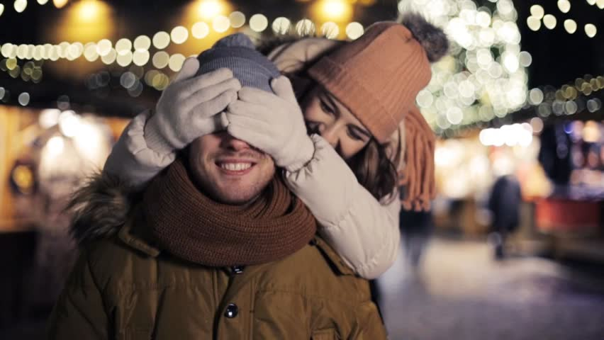 love, winter holidays and people concept - happy young couple dating having fun at christmas market in evening