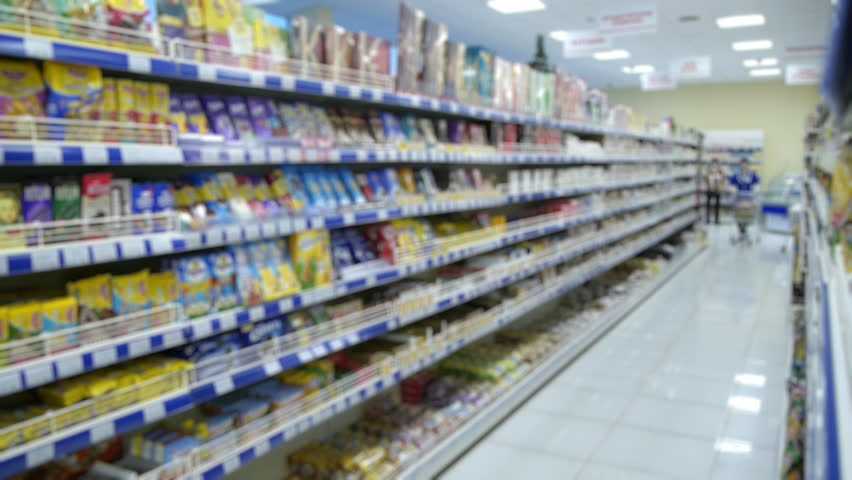 Shelves with goods in a supermarket, blurry. the girl, a store employee with a trolley | Shutterstock HD Video #22317448