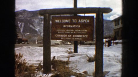ASPEN COLORADO 1961: a close up shot of a sign that says welcome to aspen from the chamber of commerce.
