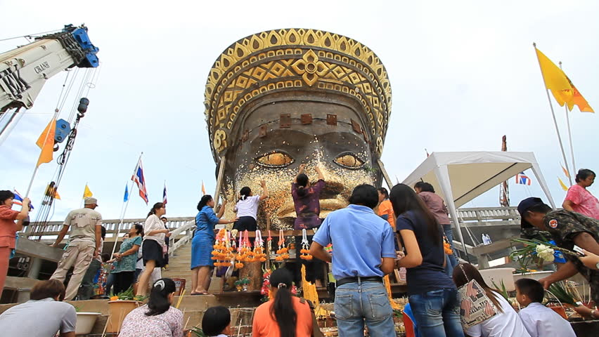 PHETCHABUN, THAILAND - JULY 15: People apply gold leafing to statue at Buddhist temple on July 15, 2011 in Phetchabun, Thailand.