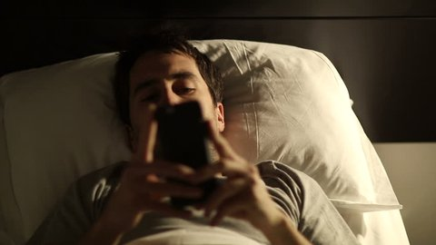 Person using cellphone in bed. Man using smartphone mobile cellphone in bed before sleeping