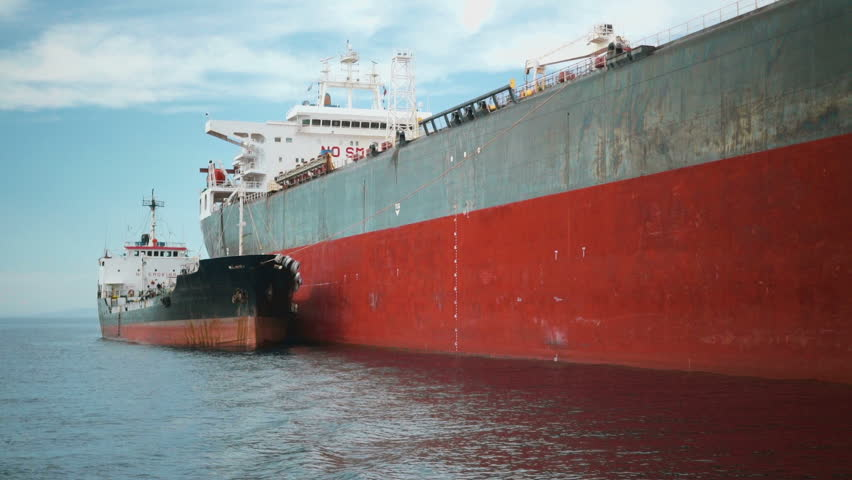 A tanker being refueled by a fuel barge in the open sea