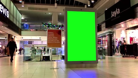 Burnaby, BC, Canada - December 06, 2016 : Green billboard for your ad beside Levis store with Christmas light was decorated full of building.