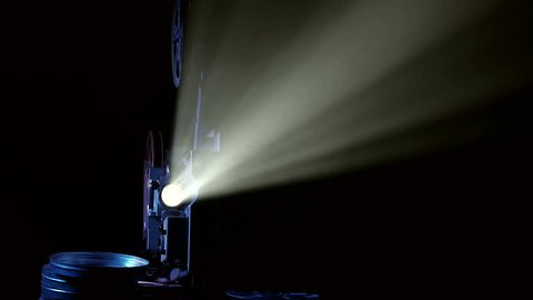 Light projector ray in dark room, changing beam in dusty air, small particles fly and glow.