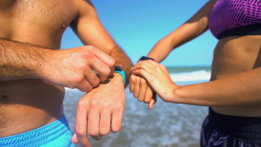 Multi ethnic male and female using sport watch technology to keep fit and healthy on their beach holiday | Shutterstock HD Video #22457548