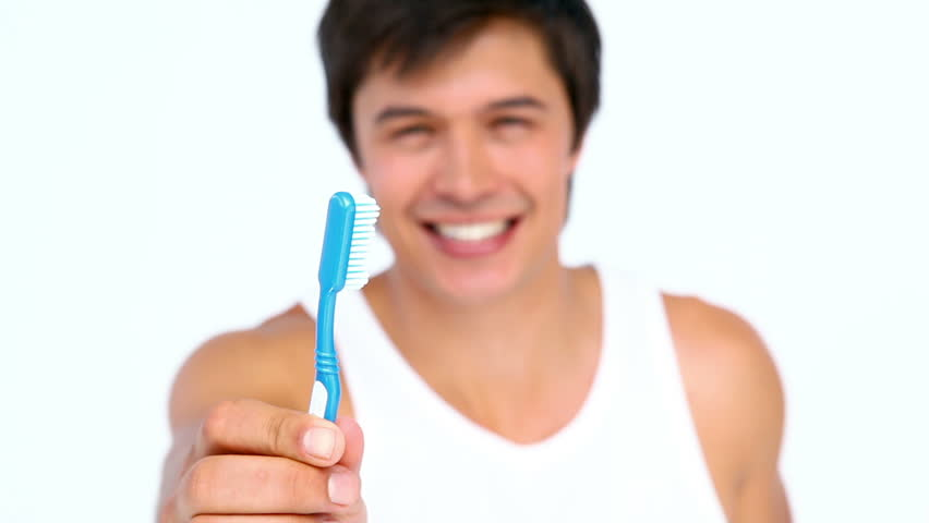 Man brushing and looking his teeth against white background