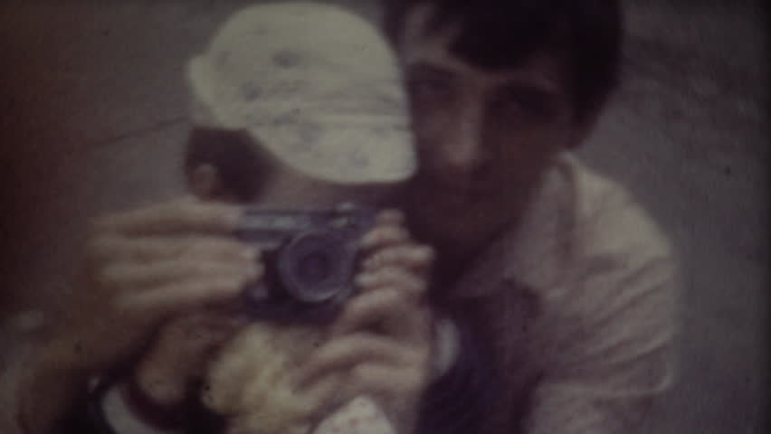 Father teaches son to photographing. Screenshot of 8mm retro camera. Family video archive.