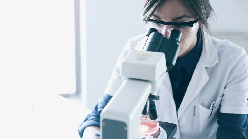 Young scientist looking through a microscope in a laboratory. Young scientist doing some research. | Shutterstock HD Video #22465618