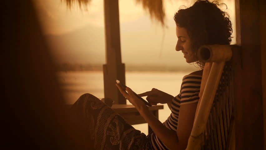 Sunset and beach on the island of Bali. The girl in a striped blouse and wide trousers in the evening sitting on a soft chair by the beach. It plays on your tablet. #22467838