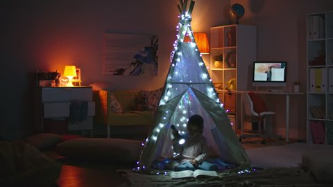 Little girl with flashlight sitting in teepee decorated with fairy lights at night and reading book