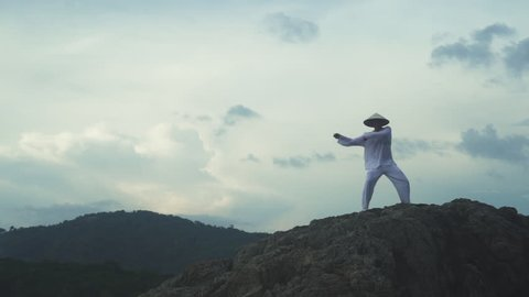 Man in white uniform training martial arts forms alone for defense training and its health benefits