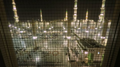 Time Lapse video in Medina Saudi Arabia. Muslim believers praying outside the al-Masjid an-Nabawi, prophet Muhammad's Mosque, during hajj season. Minarets at the background at night.