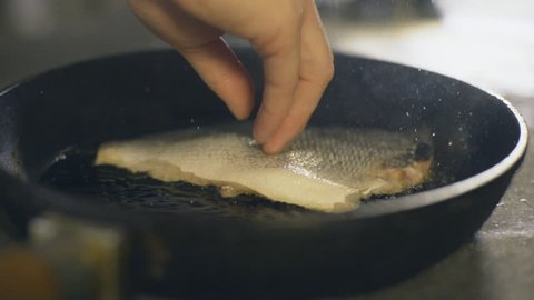 Chef is cooking fish, slow motion