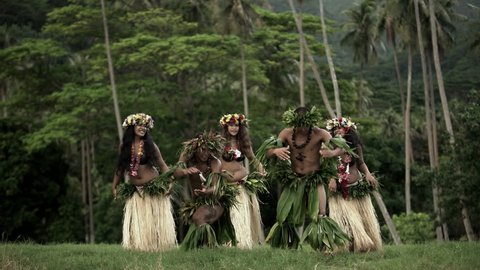 Barefoot Tahitian males in warrior dress with females in hula skirts and flower headdress performing a traditional dance at celebration ceremony South Pacific