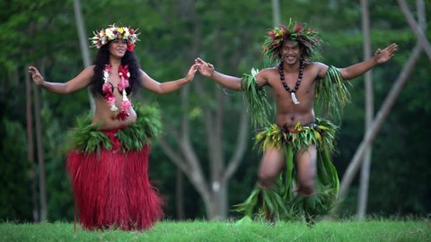 Beautiful young synchronized Polynesian male and female dancer entertaining in traditional costume barefoot outdoor French Polynesia South Pacific