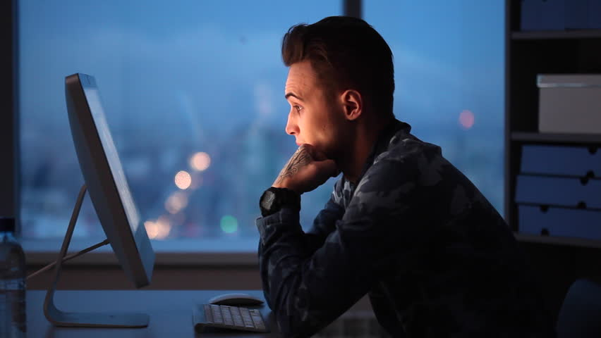 You can see young man (student, freelancer, graphic designer or creative copywriter, manager) working in agency office/Late in the Evening in the Office