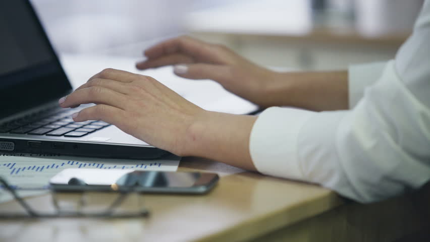 Hands of female office employee typing on laptop, inserting data in e-document
