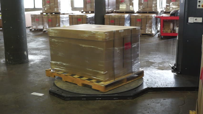 A shipping crate in wrapped in plastic on a spinning turntable machine in an industrial warehouse.