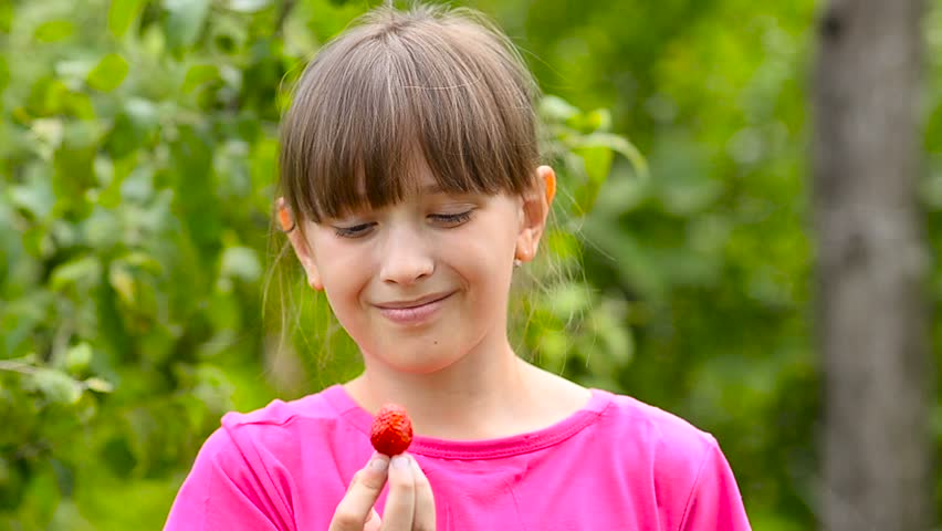 Strawberries, red, ripe, tasty, holding in the hand of a girl on the plantation and laughs. Harvest season and red sweet strawberries.