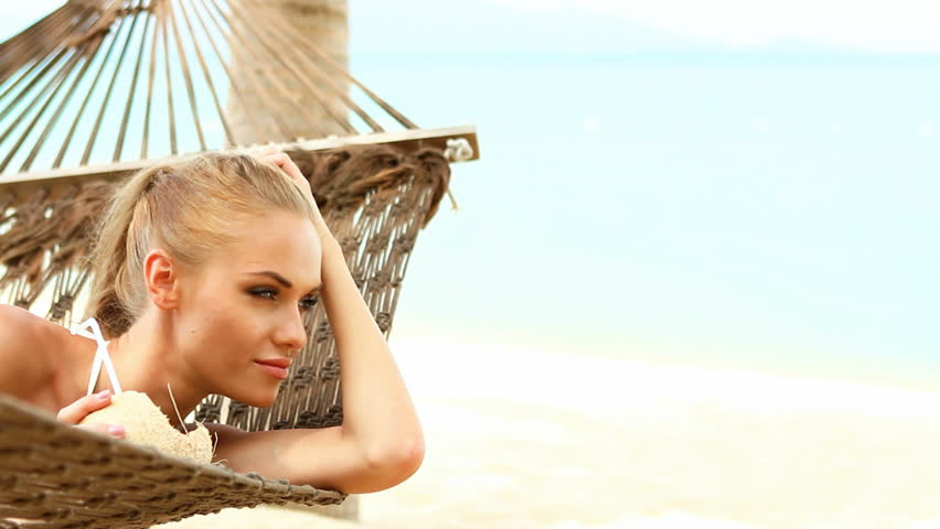 Young happy woman laying at hammock and drinking from coconut