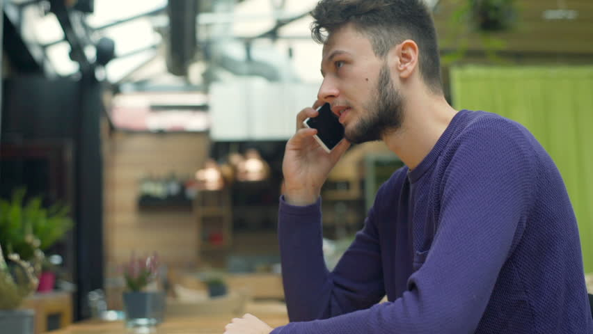 Young man sitting in the cafe and receives good news while speaking on cellphone, steadycam shot  | Shutterstock HD Video #22560748