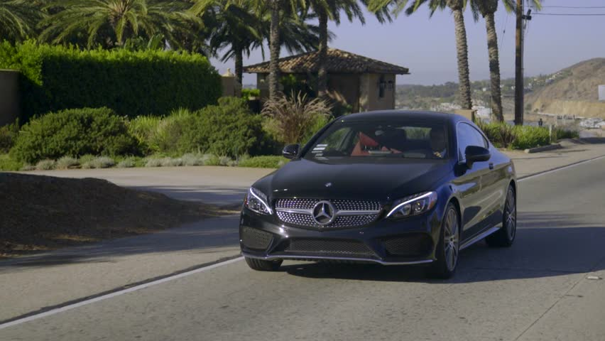 Black Mercedes C-class Coupe driving on the Malibu road