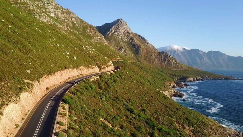 Beautiful drive through coastal road along ocean beside mountain range in south africa