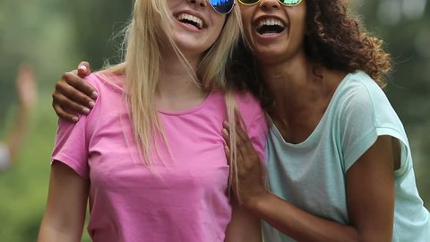 Girlfriends laughing and dancing embraced at open air music festival, having fun